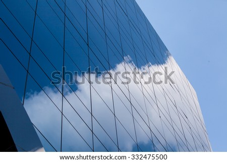 Tall business skyscraper building and window reflecting blue sky. - stock photo