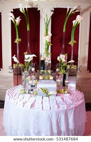 Tall callas stand in glass vases on the round table at red wall