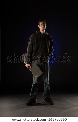 Tall casual urban young white Caucasian male holding a skateboard looking into the camera while standing.  - stock photo