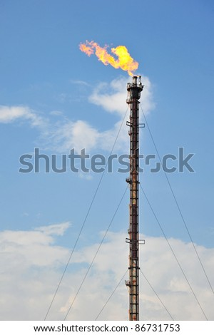 Tall Chimney Of An Oil Refinery Gas Flare - stock photo