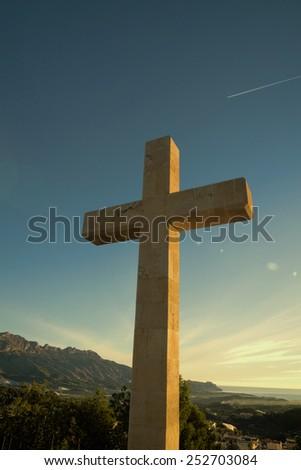 Tall Christian cross under a strong morning sun - stock photo