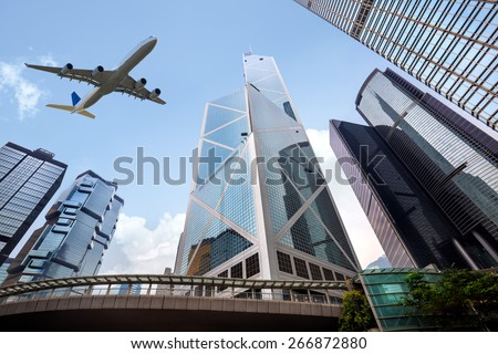 Tall city buildings and a plane flying overhead, Hong Kong - stock photo