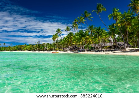 Tall coconut palm trees over tropical island resort beach in Fiji - stock photo