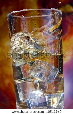 Tall, cool glass of liquid refreshment.  Dropped ice cubes form a pleasing array of splashes and bubble.