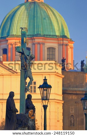 Tall cross with statue of Jesus Christ and church dome in the background, Prague, Czech Republic - stock photo