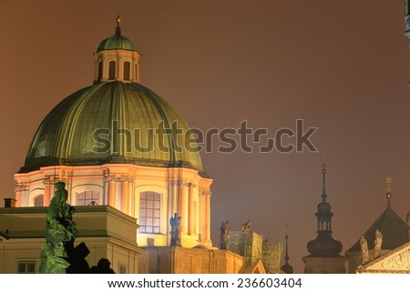 Tall dome and distant church tower dominate the sky near Charles bridge in foggy evening, Prague, Czech Republic - stock photo