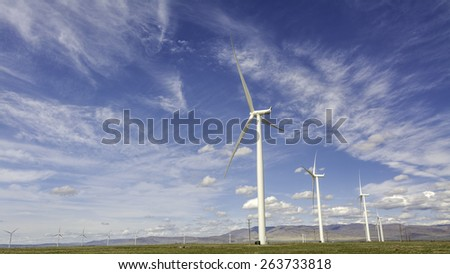 Tall electricity turbines on a windy day