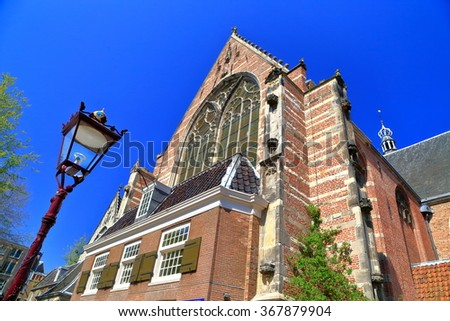 Tall facade of the Gothic building of the Oude Kerk (Old Church) in Amsterdam, the Netherlands - stock photo