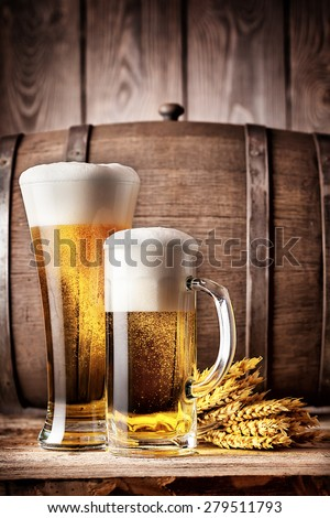 Tall glass and a mug of light beer on a background of the old wooden barrels