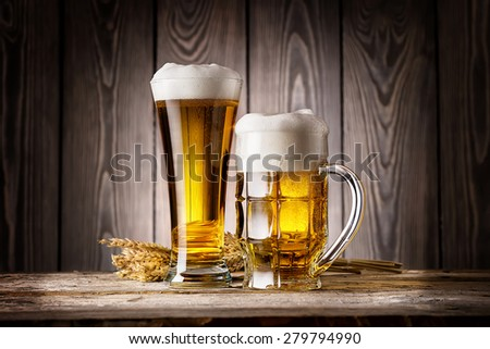Tall glass and mug of light beer with ears barley on wooden background - stock photo
