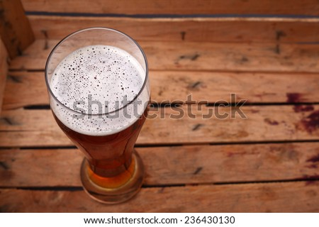 Tall glass of amber beer standing in an old dirty wooden crate - stock photo