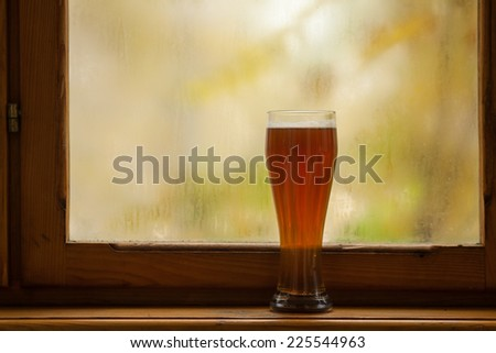 Tall glass of amber beer standing on windowsill with autumn colors in the background
