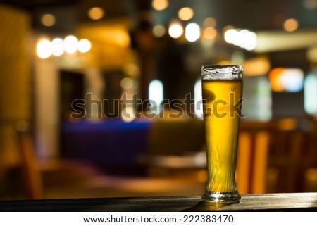 Tall Glass of Beer on Bar Counter with Blurred Background - stock photo