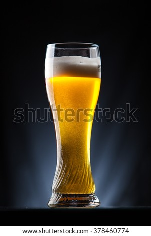 Tall glass of beer over a dark background - stock photo