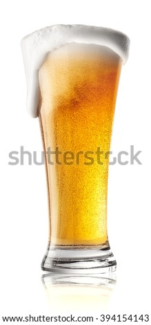 Tall glass of beer with foam spilling isolated on white background