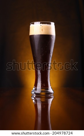 Tall glass of dark beer over a dark background lit yellow - stock photo