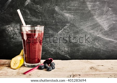 Tall glass of delicious acai berry smoothie in between a slice of banana, blueberries and plastic spoon over background with chalkboard copy space - stock photo