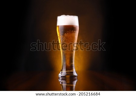 Tall glass of light beer on a dark background lit yellow - stock photo