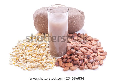 Tall glass of Mexican pozol beverage surrounded by whole corn kernels, raw cacao beans and block of ground mixture of both - stock photo