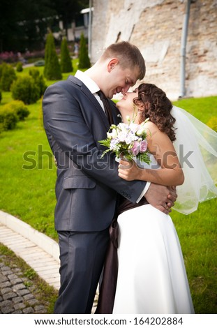 Tall handsome groom hugging happy bride at park