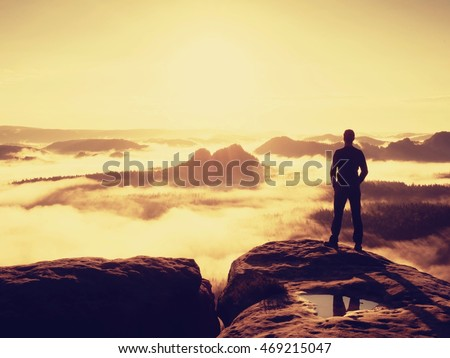 Tall hiker in black enjoying orange sunrise on view point. Heavy mist bellow in valley. Wonderful daybreak in mountains.