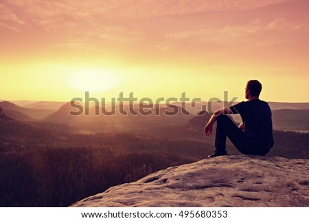 Tall hiker in mountains. Thinking man silhouette in nature within daybreak. The vignetting effect.