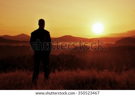 Tall hiker stand on meadow with golden stalks of grass and watch over misty and foggy morning valley to sunrise