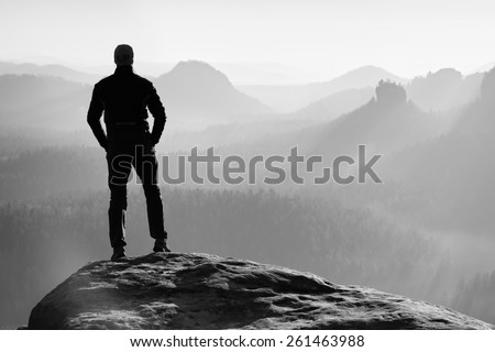 Tall hiker stand on the peak of sandstone rock in rock empires park and watching over the misty and foggy morning valley to Sun. Beautiful moment the miracle of nature  - stock photo