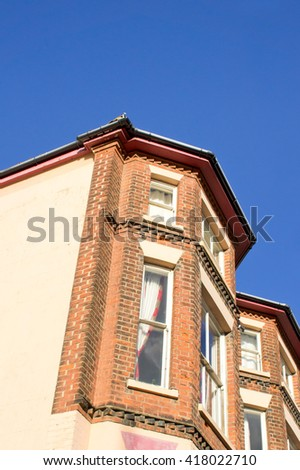 Tall houses with red brick against a blue sky - stock photo