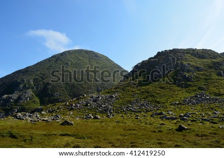 tall majestic mountain in lush green summer landscape - stock photo