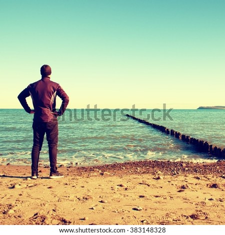 Tall man in black suit exercising and make stretching on stony beach at breakwater. Vivid and vignetting effect