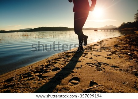 Tall man in running cloths  at amazing sunset in sport and healthy lifestyle concept and jogging cross country training workout - stock photo