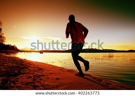 Tall man with pink windcheater and dark cap is running on sand at sunset