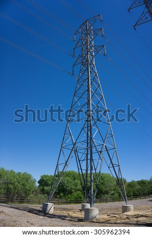 Tall metal power line tower above a walking path in Santa Clarita California. - stock photo