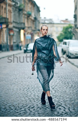 Tall model in gey clothes and freak shoes walks along the street