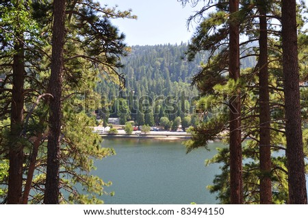 Tall pine trees frame this view of Lake Gregory in the Southern California mountains. - stock photo