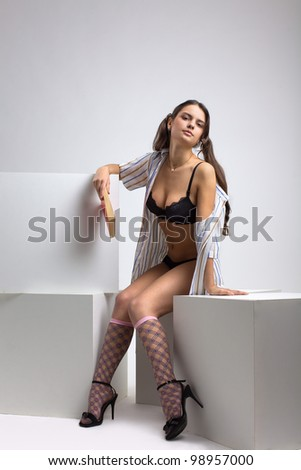 Tall sexy brunette woman in black lingerie and open shirt posing in a studio with a book - stock photo