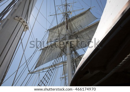 Tall ship mast and full sails looking up.