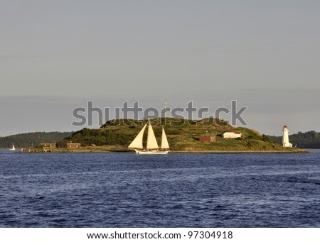 tall ship on an evening cruise circling Georges Island National Historic Site in the middle of Halifax Harbour, Nova Scotia Canada - stock photo