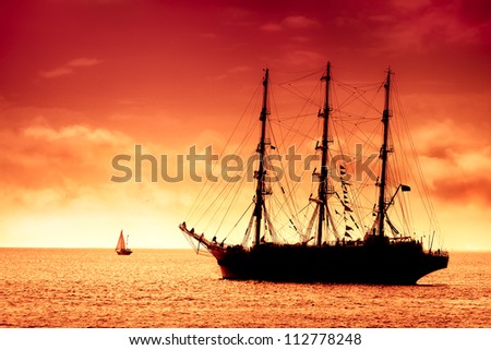 Tall ship sailing in red / Large black tall  ship on the high seas at dusk. - stock photo