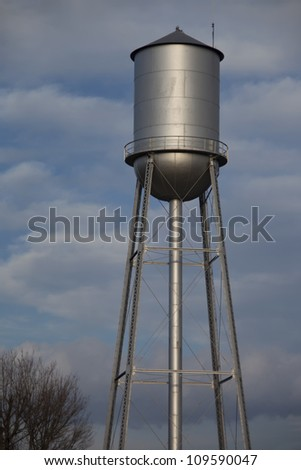 Tall silver water tower with cloudy blue sky background