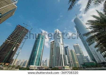 Tall skyscrapers in Dubai near water - stock photo