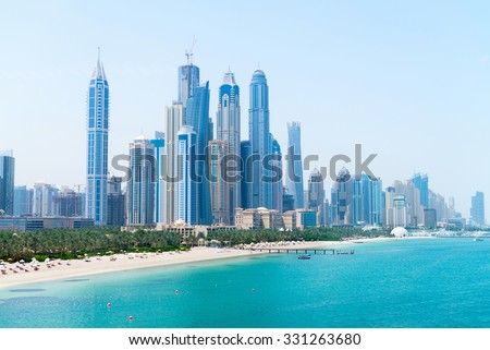 Tall skyscrapers of a modern, metropolitan cityscape tower over a beautiful, white, sandy beach on a warm, sunny day.