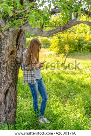 Tall slender young girl checking her mobile phone for text messages under a leafy tree in a lush green spring garden - stock photo