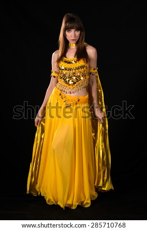 Tall slim brunette in a yellow belly dance costume - stock photo
