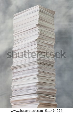 Tall stack of paper against a stormy sky