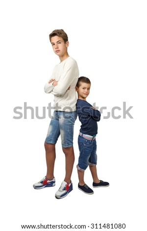 Tall teenager and little boy stand back to back with hands crossed on chest isolated on white background - stock photo