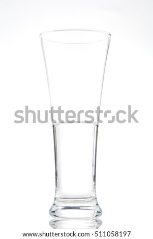 Tall thin clear glass half full of water on a white background