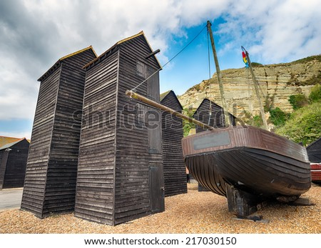 Tall thin traditional wooden fishing net huts on the harbour at the Stade in Hastings, East Sussex - stock photo
