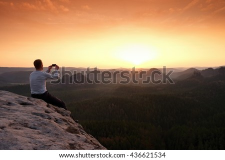 Tall tourist at dangerous cliff edge is taking selfie on peak above valley. Mountain peak and deep valley with sun in the frame